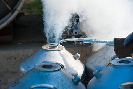 Young engineer fill with liquid nitrogen with Nitrogen storage tank at new factory Imagens