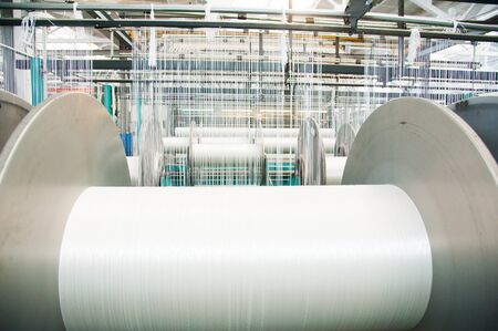 Textile industry - yarn spools on spinning machine in a textile factory Stok Fotoğraf