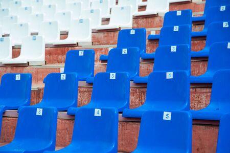 Tribune of fans at the stadium. Empty blue seats in stadium Imagens