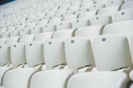 Tribune of fans at the stadium. Empty white seats in stadium