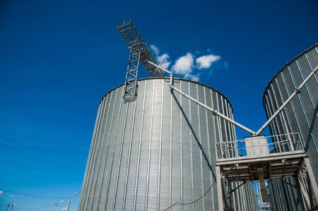 Metal grain elevator in agricultural zone. Agricultural silos against blue sky Stock Photo