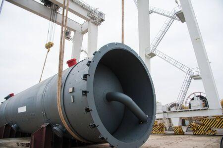 Suwnica portowa przenosząca kontener zbiornikowy. Port przemysłowy
