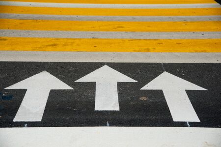 Pedestrian crossing road marking, white and yellow rectangles over gray asphalt pavement Stock Photo