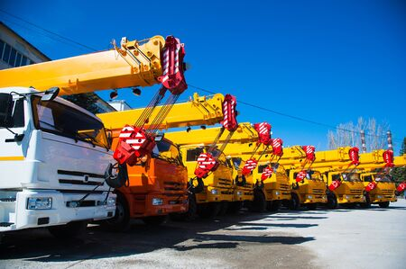 Mobile construction cranes with yellow telescopic arms and big tower cranes in sunny day. Heavy industry