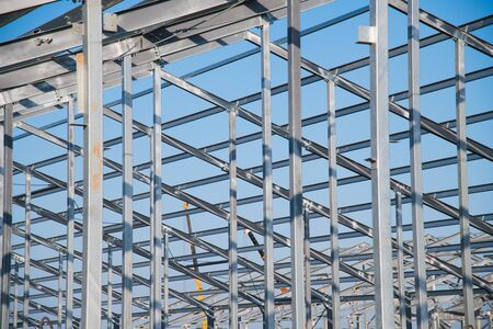 Steel frame workshop is under construction against a blue sky. New technology steel frame for construction