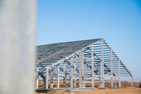 L'officina della struttura d'acciaio è in costruzione contro un cielo blu. Telaio in acciaio di nuova tecnologia per la costruzione