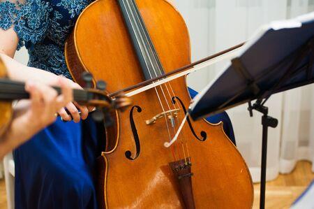 De handen van de professionele cellospeler sluiten omhoog, ze treedt op met de strijkerssectie van het symfonieorkest