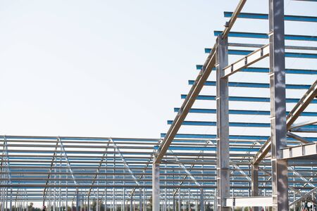 Steel frame workshop is under construction against a blue sky. New technology steel frame for construction