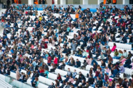 Blurred crowd of spectators on a stadium with a football match