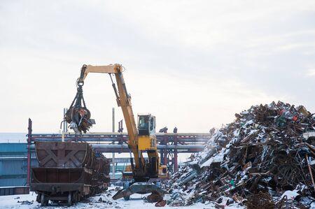 Planta de reciclaje de chatarra y chatarra de carga con grúa en un tren Foto de archivo