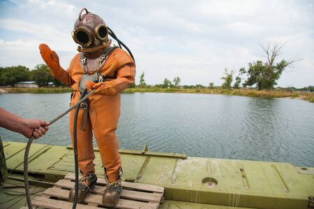 Diver immerses in a copper old vintage deep sea diving suit