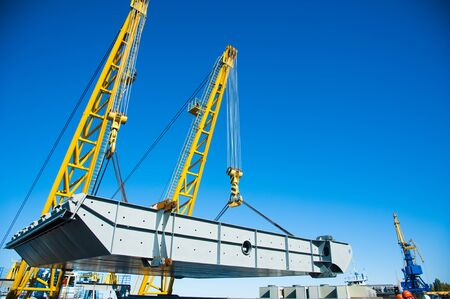 Loading in port. Floating port crane on blue sky background. Chains and hooks hoist with slings for loading in the port close-up Banque d'images