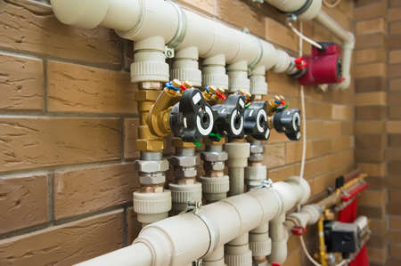 Copper valves, stainless ball valves, detector of water and plastic pipes of central heating system and water pipes in apartment during under renovation, remodeling and construction