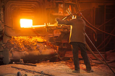 Metal structures and buildings of the old metallurgical plant inside and outside. The process of melting metal. Steelworker at work. Products of the metallurgical enterprise.