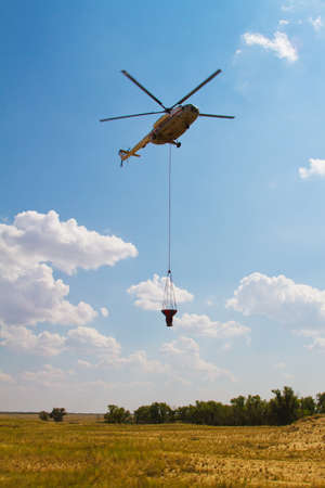 Firefighting helicopter with fire bucket flies against a clear blue sky