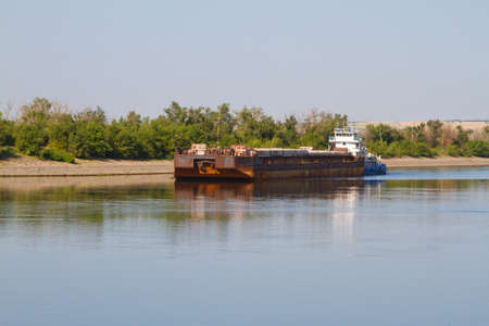 Cargo ship moving along the river, summer sunny day