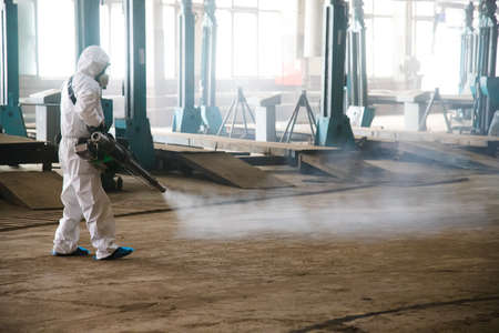 Worker in a protective suit handles industrial premises, buildings, and interiors to protect against COVID-19 infection. Epidemic. Coronavirus
