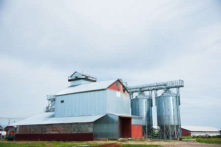 Metal grain elevator in agricultural zone. Agricultural silos against blue sky 免版税图像
