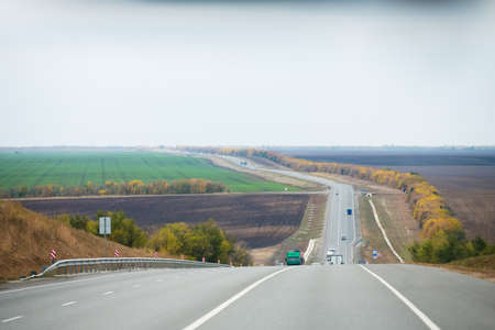 The amount of traffic. Intercity highway in cloudy autumn. Road. Landscape