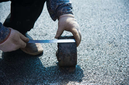 Checking the quality of asphalt by taking samples and measuring the thickness of asphalt. Construction. Repair of roads