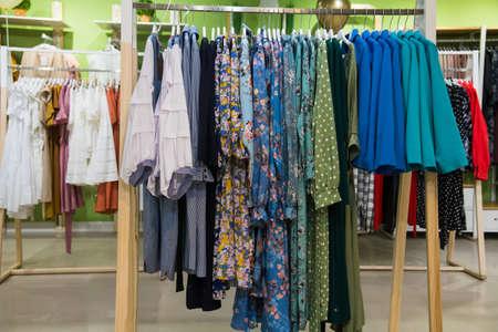 Colorful women's dresses on hangers in a retail shop Standard-Bild