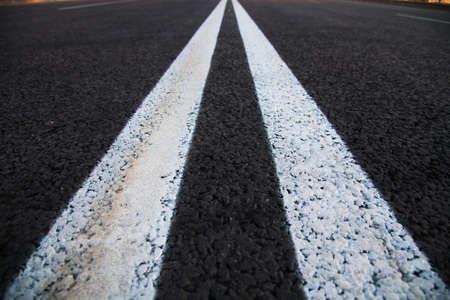 Road markings on asphalt on the street. White dividing line and special road marking symbols on black asphalt
