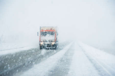 A lone truck driving on a winter road in a snowfall