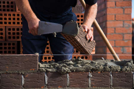 Bricklayer worker installing brick masonry on exterior wall. Professional construction worker laying bricks.