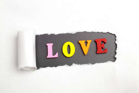 The word love on a black background in multicolored letters, with a piece of white paper. Archivio Fotografico
