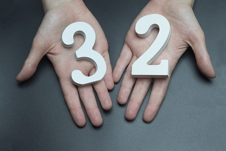 female hand with number thirty-two.