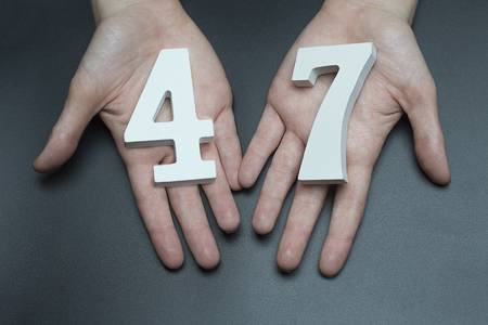 Female hand with number forty-seven.