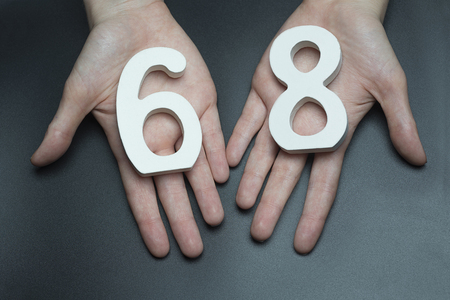 Female hand with number sixty-eight.
