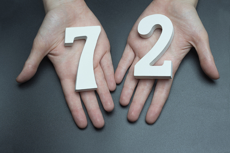 Female hand with numbers seventy-two.