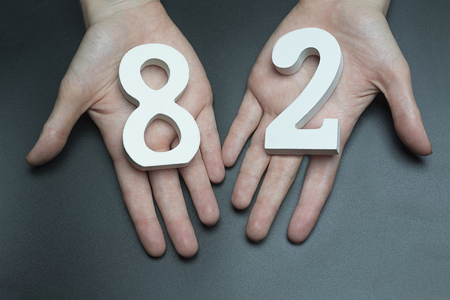 Female hand with numbers eighty-two.