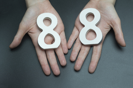 Female hand with numbers eighty-eight. Imagens