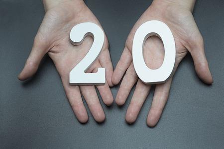 Female hand with number twenty.