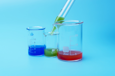 Laboratory glasses and pipette with green, blue and red liquid on a blue background Stock Photo