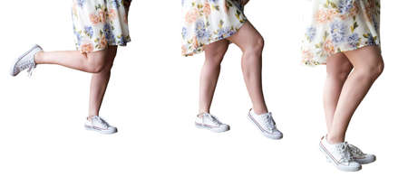 Beautiful slender female legs on a white  in sneakers.