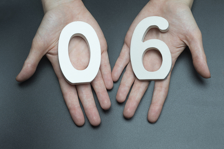 Female hand with a digit to a zero and six.