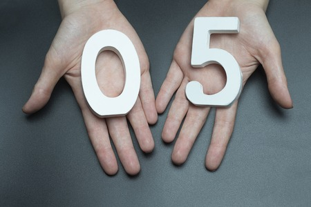Female hand with a digit to a zero and five.
