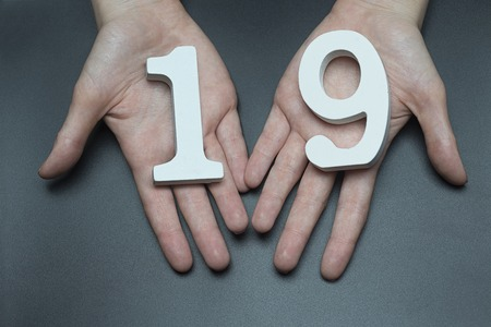 Female hand with number nineteen.