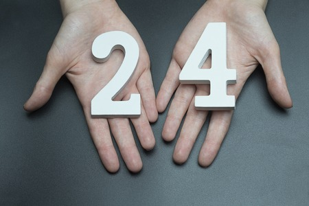 Female hand with number twenty-four.