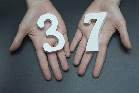 Female hand with number thirty-seven.