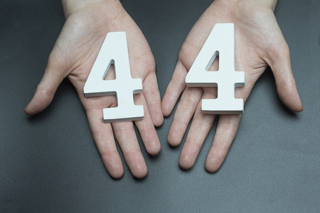 Female hand with number forty-four.
