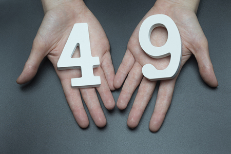 Female hand with the number forty-nine.