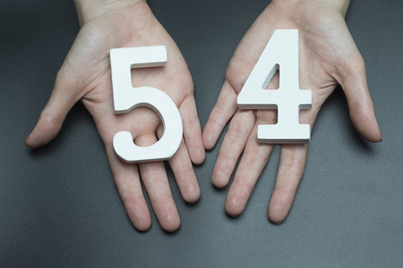 Female hand with number fifty-four.