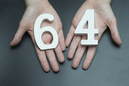 Female hand with number sixty-four. Banco de Imagens