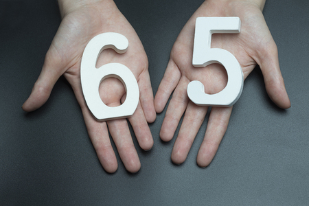 Female hand with the number sixty-five.