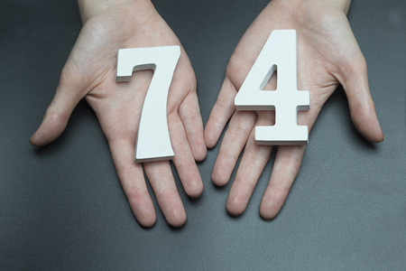 Female hand with numbers seventy-four.