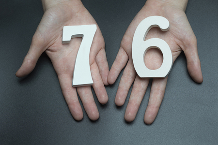 Female hand with numbers seventy-six. Imagens